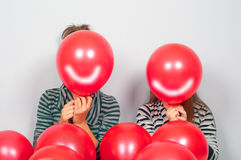 Teenage girls hiding their faces behind balloons Royalty Free Stock Images