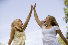 Teenage girls High-Five. Teen girls celebrate winning by jumping in air and doing a high-five Royalty Free Stock Image