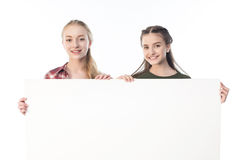 Teenage girls holding blank banner isolated on white Royalty Free Stock Image
