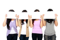 Teenage girls holding white board Stock Photos