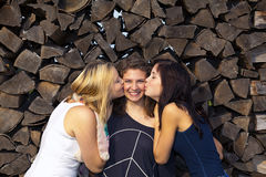 Teenage girls kissing their girl friend. Two teenage girls kissing their laughing girl friend in the middle on her cheeks Stock Images
