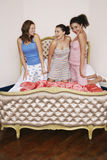 Teenage Girls Kneeling On Funky Bed Royalty Free Stock Photo
