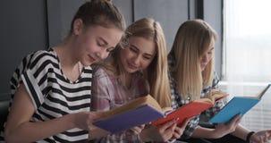 Joyful teenage girls reading books stock footage