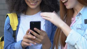 Teenage girls laughing at social media posts about classmates, cyberbullying. Stock footage stock video