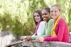 Teenage Girls Leaning On Wooden Railing Stock Photography