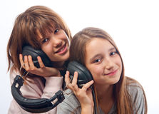 Teenage girls listen to music through headphones Stock Images