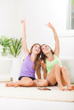 Teenage girls listening music. Two Beautiful teenage girls sitting on the carpet and listening music from tablet pc Royalty Free Stock Photography