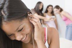 Teenage girls listening to music. Stock Photos