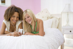 Teenage Girls Lying On Bed Listening To Mp3 Player Royalty Free Stock Images