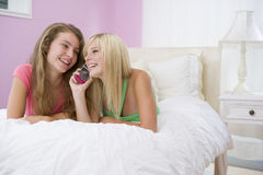 Teenage Girls Lying On Bed Using Cell Phone Stock Images