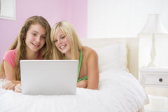 Teenage Girls Lying On Bed Using Laptop Royalty Free Stock Images