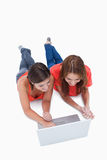 Teenage girls lying down while looking at a laptop Stock Image