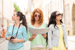 Teenage girls with map and camera Royalty Free Stock Photography