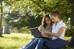 Teenage girls in the park using a laptop Royalty Free Stock Photos