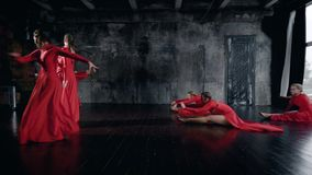 Teenage girls are performing dance in a rehearsal room, wearing red dresses, leaping and whirling. Training for performance stock video footage