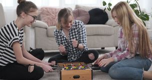 Teenage girls playing foosball at home. Excited teenage girl friends playing foosball at home stock video