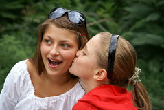 Teenage girls playing outdoors. Two beautiful cheerful teenage girls kissing outdoors Royalty Free Stock Photos