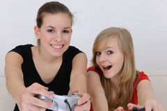 Teenage girls playing playstation. At home stock photography
