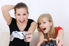 Teenage girls playing playstation. Excited teenage girls playing playstation at home Stock Photos