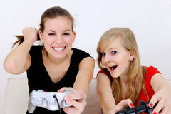 Teenage girls playing playstation. Happy teenage girls playing playstation at home stock images