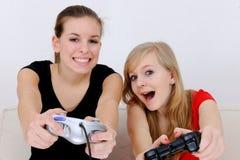 Teenage girls playing playstation. Happy teenage girls playing playstation royalty free stock photography