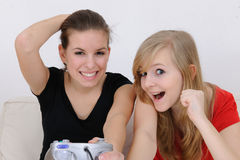 Teenage girls playing playstationteenage girls pla. Happy teenage girls playing playstation royalty free stock photography