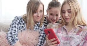 Teenage girls reading social media content on mobile phone. Three teenage girls reading social media content on mobile phone at home stock video footage