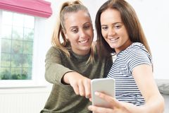Teenage Girls Reading Text Message On Mobile Phone Stock Photos
