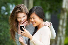 Teenage Girls Reading Text Message Together Stock Images