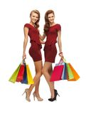 Teenage girls in red dresses with shopping bags Royalty Free Stock Photo