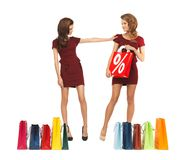 Teenage girls in red dresses with shopping bags Royalty Free Stock Images