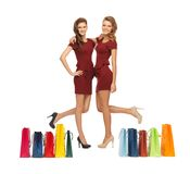 Teenage girls in red dresses with shopping bags Royalty Free Stock Photos