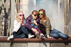 Teenage girls relaxing against a city fountain Stock Image