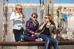 Teenage girls relaxing against a city fountain Royalty Free Stock Image