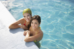 Teenage Girls Relaxing At The Edge Of Swimming Pool Stock Image