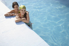 Teenage Girls Relaxing At The Edge Of Swimming Pool Royalty Free Stock Photos