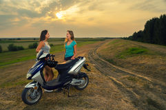 Teenage girls resting after riding motorcycle. Teenage girls resting in the nature after riding scooter on beautiful summer evening Royalty Free Stock Photography