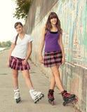 Teenage girls on roller skates having fun stock images