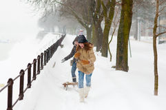 Teenage girls running under the falling snow Stock Images