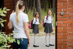 Two teenage girls in school uniform leaving home to school. Teenage girls in school uniform leaving home to school royalty free stock images