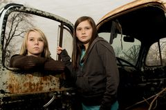 Teenage girls with serious look. Girls with serious standing outside by an old truck royalty free stock images