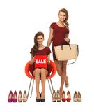Teenage girls with shoes, bag and sale sign Royalty Free Stock Photos