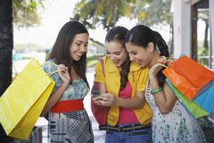 Teenage Girls With Shopping Bags Text Messaging Stock Image
