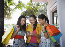 Teenage Girls With Shopping Bags Text Messaging. Happy teenage girls with shopping bags text messaging outdoors Royalty Free Stock Image