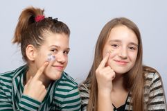 Teenage girls showing hearts on their faces Stock Images