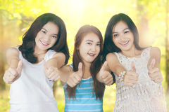 Teenage girls showing thumbs up in nature Royalty Free Stock Image