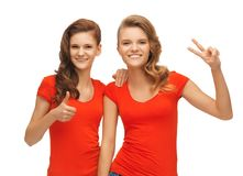 Teenage girls showing thumbs up and victory sign Royalty Free Stock Images