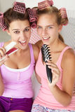 Teenage girls singing into hairbrushes Royalty Free Stock Photo