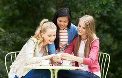 Teenage Girls Sitting At Outdoor cafeWith Mobile Phone Stock Photo