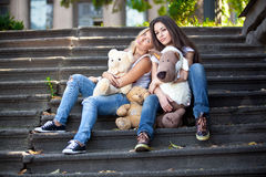 Teenage girls sitting on stairs outdoor and holding teddy bears Royalty Free Stock Photos
